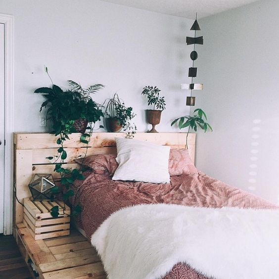 Conjunto de cama, cabecero y mesita de noche hechos con palets